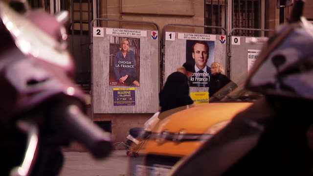 vidéos et rushes de french presidential candidates; marine le pen & emmanuel macron present on the posters on the streets of the countries capital, ahead of the 2017... - poste