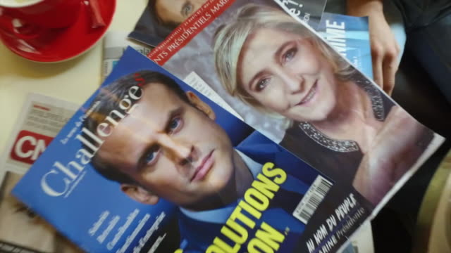 french presidential candidates marine le pen emmanuel macron shown on the front cover of magazines ahead of the 2017 election - 雑誌点の映像素材/bロール