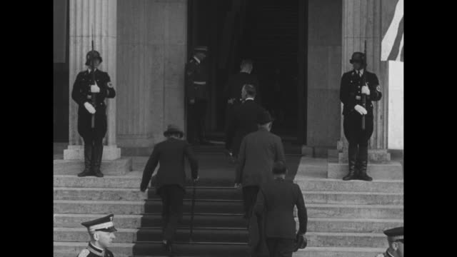stockvideo's en b-roll-footage met french prime minister edouard daladier and british prime minister neville chamberlain walk up steps of the fuhrerbau, where meeting concerning adolf... - nazi vlag