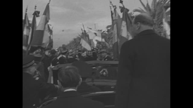 VS French Prime Minister Edouard Daladier rides in convertible automobile with uniformed officer and dignitary / VS he and others stand saluting...