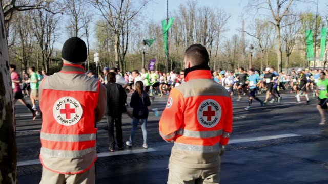 french red cross watching runners on champs elysées avenue during the sport event marathon of paris 2016 - red cross stock videos & royalty-free footage