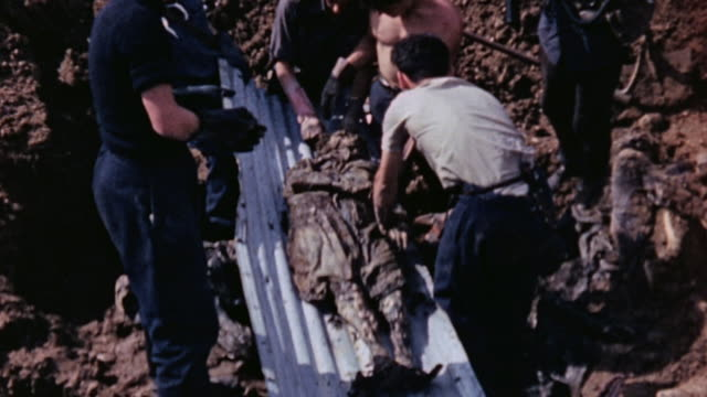 French Red Cross workers excavating a corpse from mass grave / Lyons France