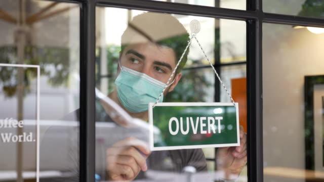 stockvideo's en b-roll-footage met franse opening kleine bedrijven tijdens covid-19 pandemie - bord open