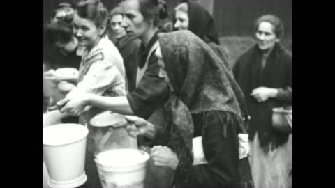vidéos et rushes de french soldier serves food to women at outdoor soup kitchen / woman takes pail and dumps bowl into it as another woman hands over her bucket and... - ruhr