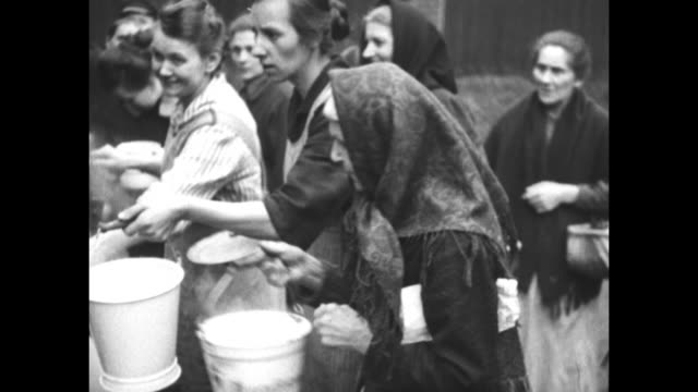 MS French soldier serves food to women at outdoor soup kitchen / MS woman takes pail and dumps bowl into it as another woman hands over her bucket...