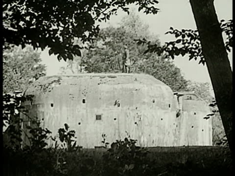 vídeos de stock e filmes b-roll de french soldier standing on top of tall maginot line casemate w/ rifle trees forest bg fg - linha maginot