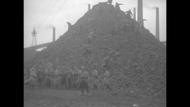 french soldier stands with rifle next to men shovel coal on coal pile / men walk down large pile of coal / vs polish laborers shovel coal onto train... - 1920 stock-videos und b-roll-filmmaterial