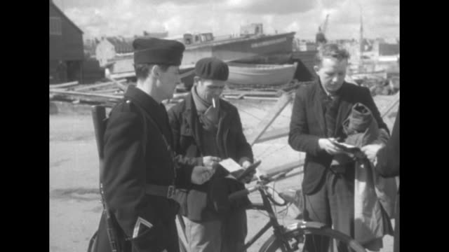 vs french soldiers in long coats at checkpoint they examine documents of bicyclist and others / barbedwire barricade near dock / barbed wire in... - la manche stock videos and b-roll footage