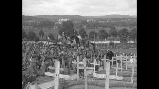 vídeos y material grabado en eventos de stock de french soldiers march through saintmihiel and up a hill at the american cemetery / men holding french regimental flags / general aldebert de chambrun... - rodear