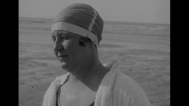 cu french swimmer jeanne sion standing on beach posing for photo opportunity and talking to camera / rear shot sion and man walking away from camera... - english channel stock videos & royalty-free footage