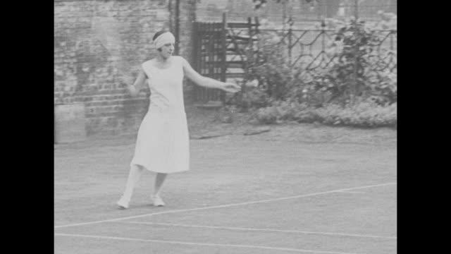 vidéos et rushes de french tennis player suzanne lenglen in tennis outfit / cus lenglen's left and right hands/wrists holding racket / vs she demonstrates tennis serves... - terrain de jeu