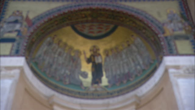 A fresco in St. Peter's Basilica depicts hand painted religious figures.