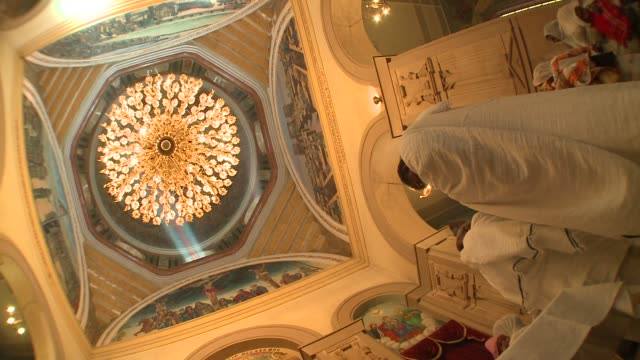 Frescoes surround a chandelier in a church dome. Available in HD.
