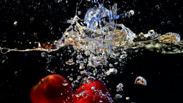 fresh apples slowly falling in water, healthy snack, source of vitamin. - apple fruit stock videos & royalty-free footage