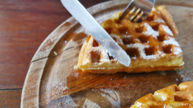 fresh baked waffle topped with honey syrup is cut into smaller pieces - waffles stock videos and b-roll footage