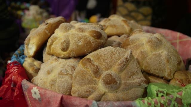 vídeos de stock e filmes b-roll de fresh bread in the basket to celebrate day of the dead in patzcuaro, janitzio island in michoacan state - pão