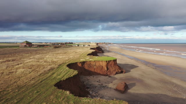 vídeos de stock, filmes e b-roll de fresh cliff falls show the devastation caused by coastal erosion of the cliff face in the village of aldbrough in the east riding of yorkshire on... - erodido