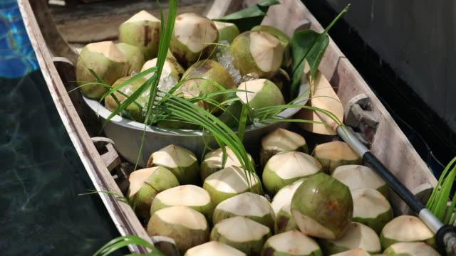 vídeos de stock, filmes e b-roll de cocos frescos no barco, no mercado flutuante na tailândia. - vender