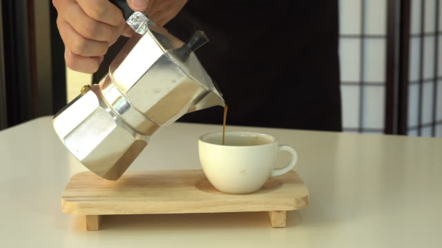 fresh coffee pouring from mokapot into cup. - aluminum stock videos and b-roll footage