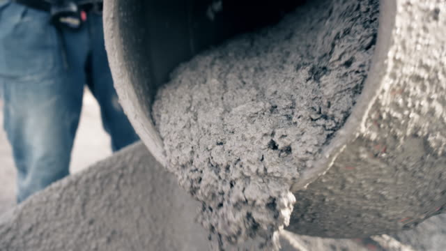 slo mo fresh concrete being poured out of the drum of the concrete mixer - construction industry stock videos & royalty-free footage