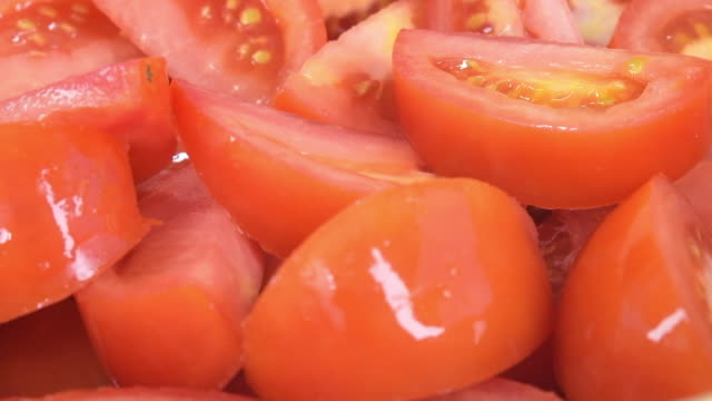 Fresh cut tomato pieces, the fall in slow motion inside a wooden bowl