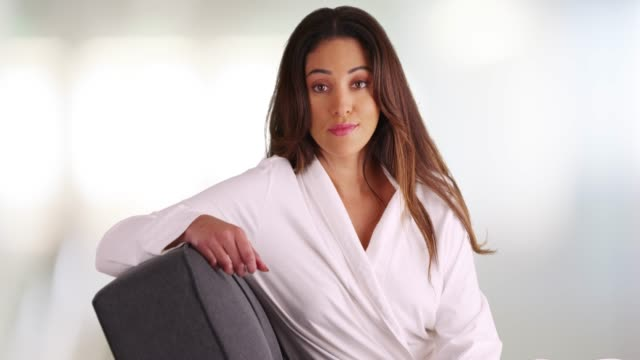 fresh faced latina woman lounging on couch at day spa, looking at camera - psychiatrist's couch stock videos & royalty-free footage