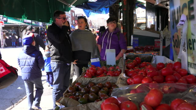 Fresh fruit and vegetable market and people around it Kensington Market is a distinctive multicultural neighbourhood in Downtown Toronto Ontario...