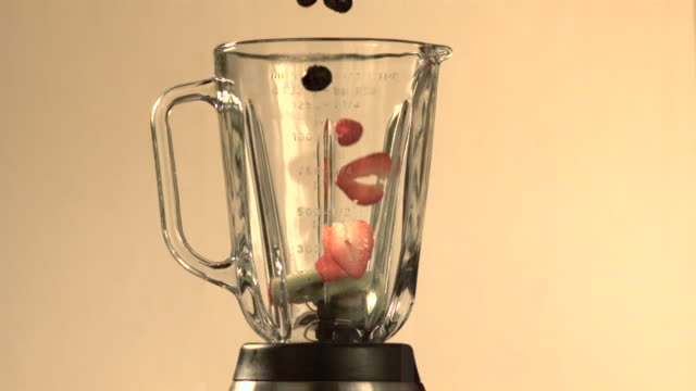 Fresh fruit falling into blender (slow motion)