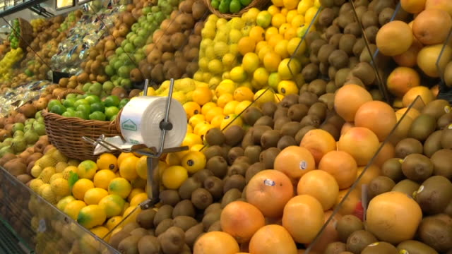 Fresh fruit on display in produce section of supermarket including apples lemons kiwifruit grapefruit pears and limes