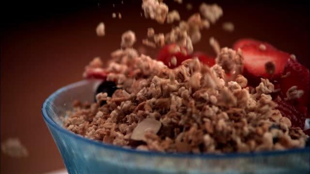 slo mo, cu, fresh fruits and granola being poured into bowl of milk  - breakfast cereal stock videos & royalty-free footage