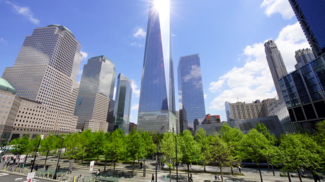 fresh green trees grow and surround the 9/11 memorial in spring at lower manhattan new york. one world trade center and the other lower manhattan skyscrapers stand behind the 9/11 memorial. clouds move over the skyscrapers. - world trade center manhattan video stock e b–roll