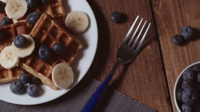 fresh homemade belgian waffles with blueberries and banana for breakfast - syrup stock videos & royalty-free footage