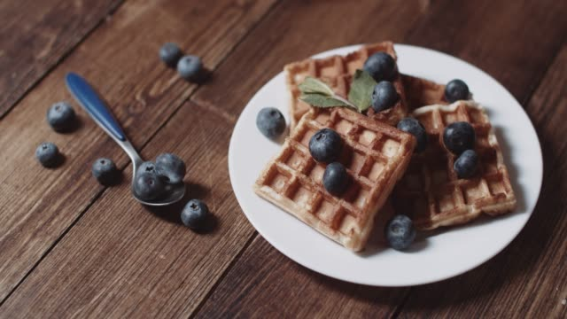 vídeos y material grabado en eventos de stock de gofres belgas caseros frescos con arándanos para el desayuno - waffles