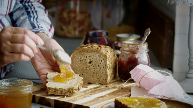 fresh homemade brown bread with marmalade - brown bread stock videos and b-roll footage