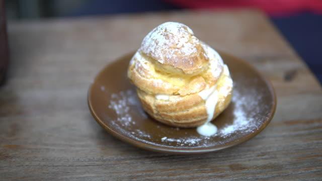fresh homemade choux cream with vanilla custard filling on top with sugar icing. - custard stock videos & royalty-free footage