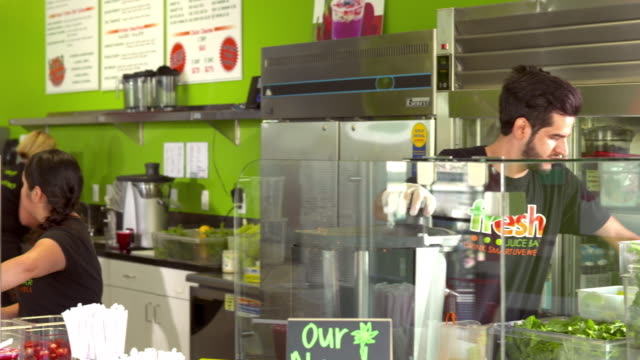 WS PAN fresh juice bar retail store employees squeezing fresh organic juices while girl at cash register rings up a purchase