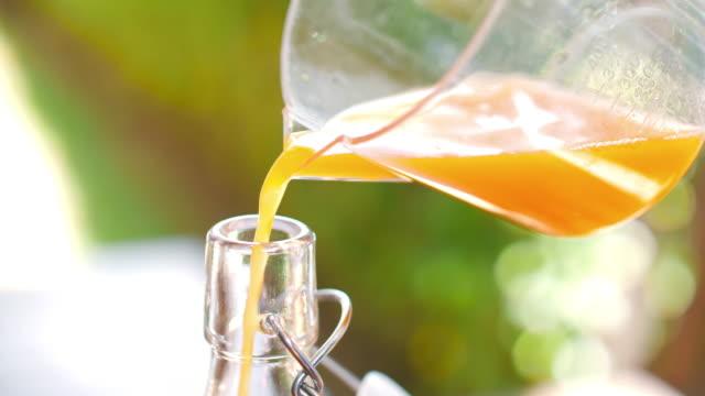 fresh orange juice poured into a glass , slow motion - orange juice stock videos & royalty-free footage