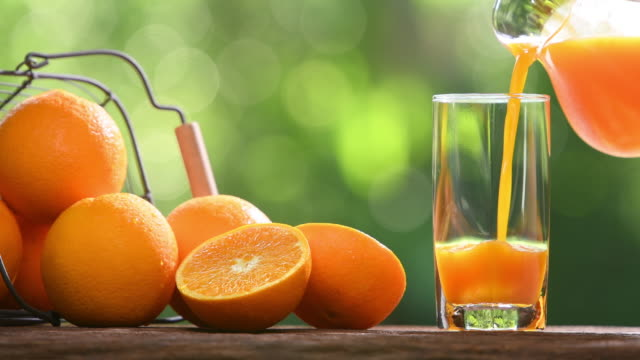 Fresh orange juice pouring into glass