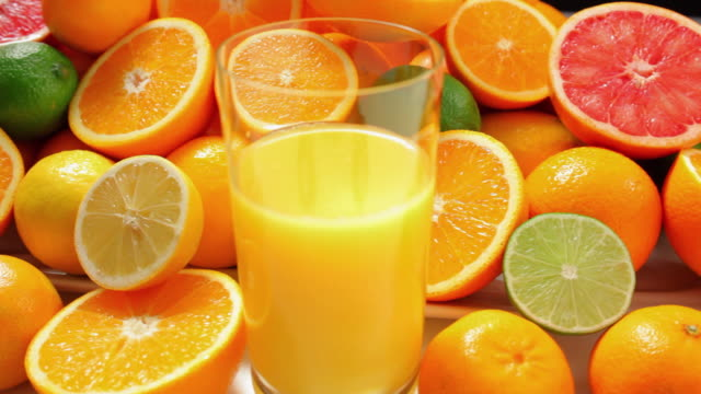 cu fresh oranges and limes with glass of juice / london, united kingdom - inquadratura dall'alto di un tavolo video stock e b–roll
