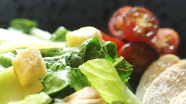 vidéos et rushes de salade de légumes mélangés biologiques frais sur l'assiette. - salade verte