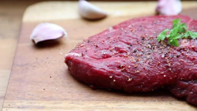 fresh organic steak on wooden cutting board with salt, pepper and garlic - raw food stock videos & royalty-free footage