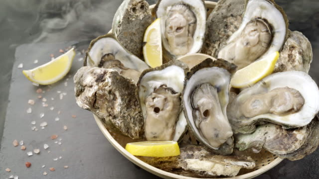 4k uhd: fresh oysters in wooden basket with lemon and himalayan salt on black plate with flow of frozen icy smoke. fresh luxury seafood and menu recipes retail market concept. - crustacean stock videos & royalty-free footage