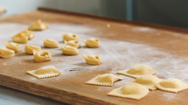 fresh pasta parcels lie on wooden board - wide stock videos and b-roll footage