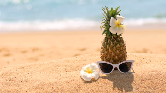 fresh pineapple and sunglasses on tropical beach. - tropical flower stock videos & royalty-free footage