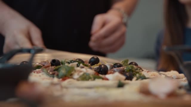 fresh pizza being placed on table with paddle / peel, close up - black olive stock videos & royalty-free footage