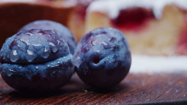 fresh plums against homemade plum pie. close-up - plum stock videos & royalty-free footage