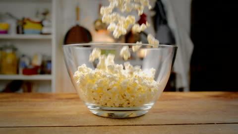 fresh popcorn falling into bowl - popcorn stock videos & royalty-free footage