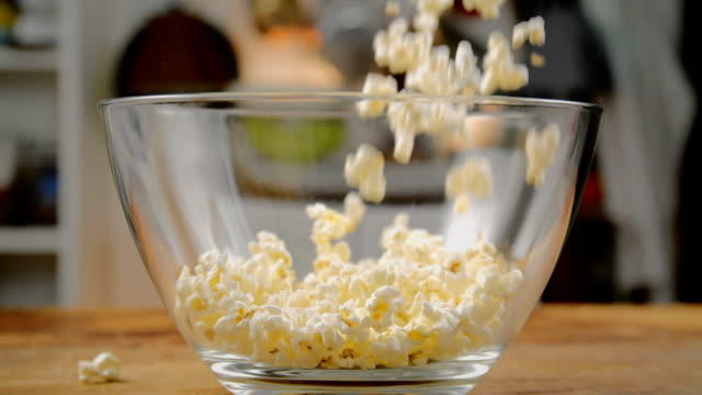 fresh popcorn falling into bowl - popcorn stock videos & royalty-free footage