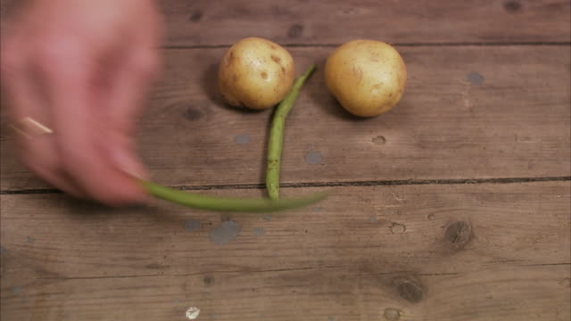 fresh potatoes and beans making a happy face sweden. - グリーンビーンズ点の映像素材/bロール