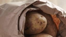 fresh potatoes in kraft paper bag on oak table